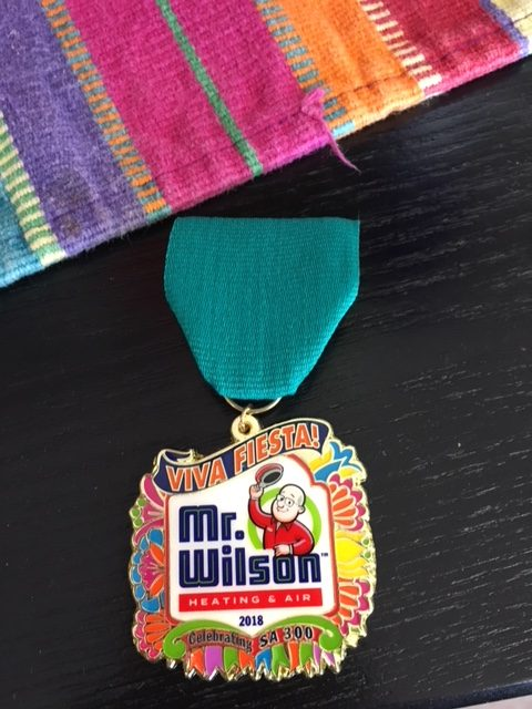 Mr Wilson Heating & Air Conditioning Introduces Our New Logo Alongside Our 2018 San Antonio Fiesta Medal